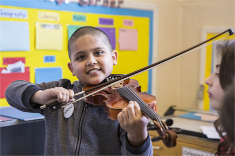 Pupil trying the violin for the first time